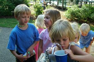 children drinking from a water cooler and fountain